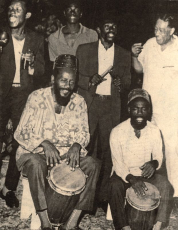 Duke Ellington snaps his fingers to Count Ossie (seated, left) and the Mystic Revelation of Rastafari