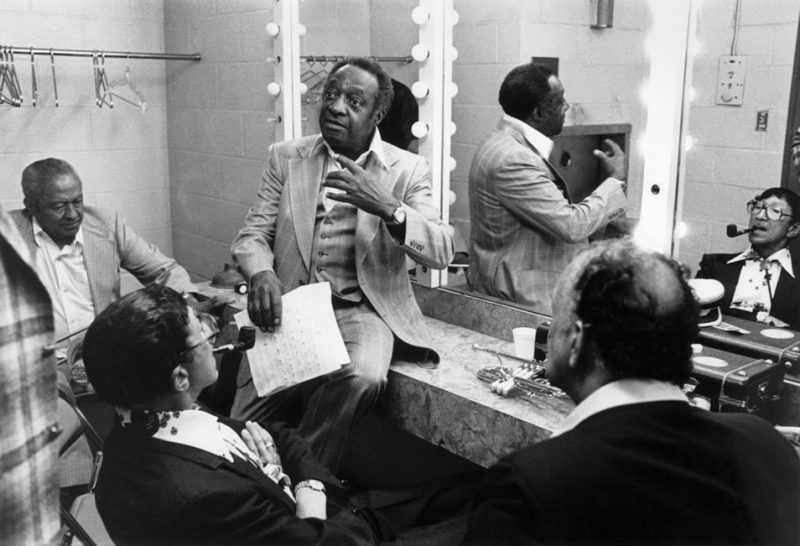 "Backstage at Jack Kleinsinger's ""Highlights in Jazz"" concert, New York University, June 1979. L to R: Dicky Wells, Doc Cheatham (back to camera and reflected, right, in mirror), Milt Hinton and Earl Warren (back to camera)."