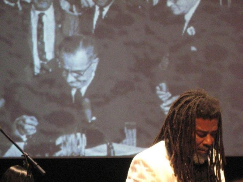 Wadada Leo Smith in front of projection of LBJ signing Voting Rights Act of 1964 in performance of Ten Freedom Summers in October 2011
