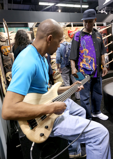 A tradeshow attendee plays Ibanez's GWB205ENTF Gary Willis signature bass at NAMM 2016