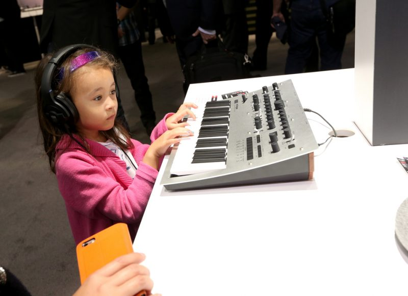 A young tradeshow attendee plays the affordable new Korg Minilogue Polyphonic Analog Synthesizer, NAMM 2016