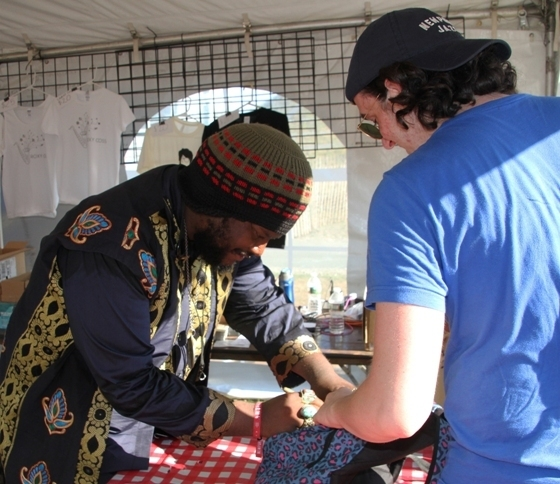 Kamasi Washington signs a fan's backpack at the 2016 Newport Jazz Festival