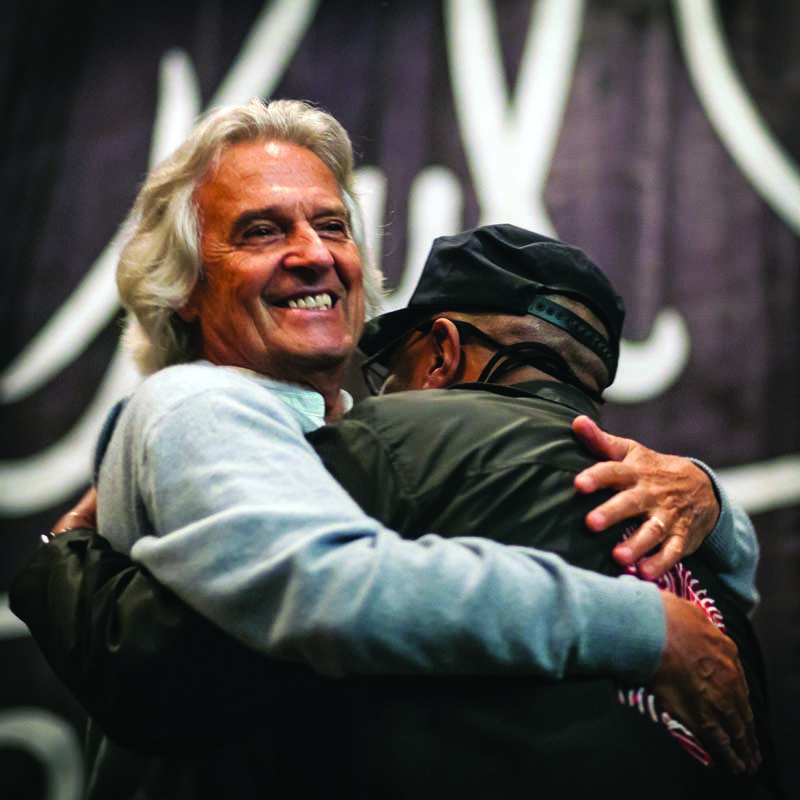John McLaughlin embraces Dennis Chambers in Baltimore in 2015