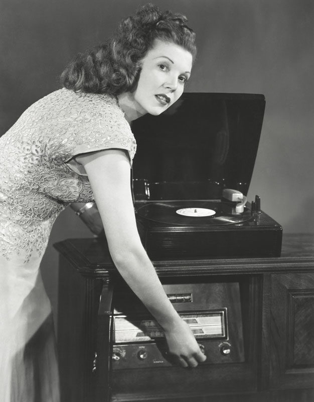 Vintage image of a women playing an album on a stereo system