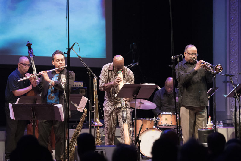 "Craig Harris (center) switches from trombone to didgeridoo for a performance of his ""Brown Butterfly"" with (L to R) Calvin Jones, Jay Rodriguez, Tony Lewis, and Eddie Allen at Roulette, May 27, 2018"
