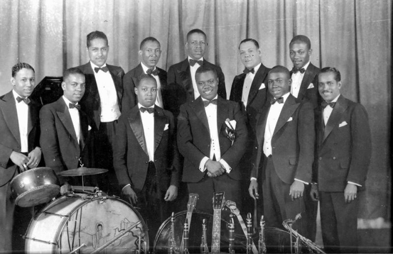 Louis Armstrong with the Luis Russell Orchestra, December 1929 (Russell is next to Armstrong, second from right in the lower row)(courtesy of the Louis Armstrong House Museum)