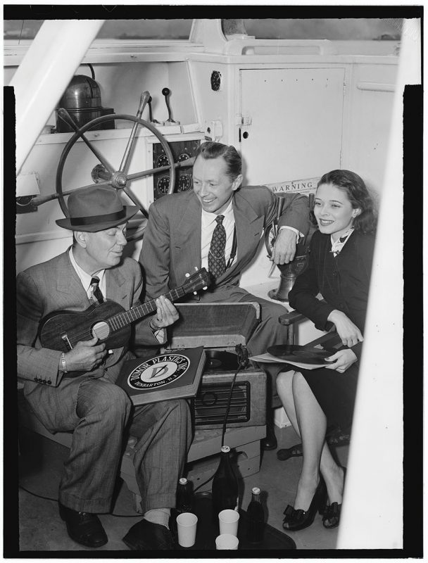 """Cliff Edwards (left) with singers Frank Raye and Betty Brewer on his """"Ukulele Lady"""" yacht, June 1947 (photo: William P. Gottlieb Collection, Library of Congress)"""